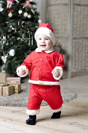 Baby in Santa costume walking near decorating Christmas tree Stock Photo - 22970338