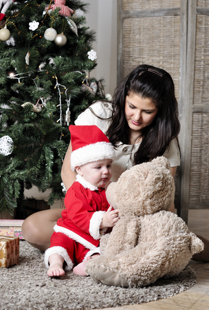 Baby in Santa costume sit with mother near Christmas tree with teddy bear photo