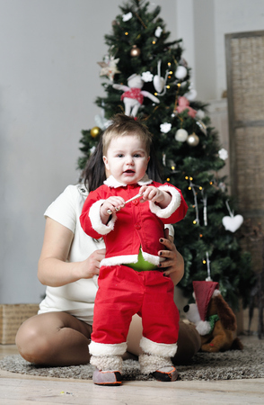 Baby in Santa costume standing with mother on decorating Christmas tree photo