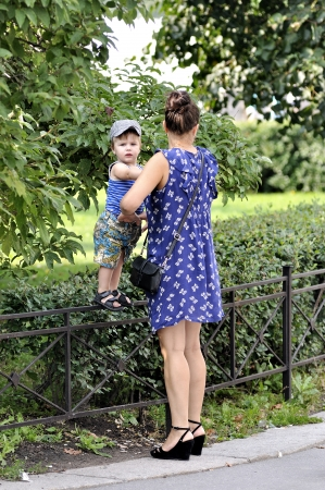 child protection: Mother holds little child who stay on a garden protection