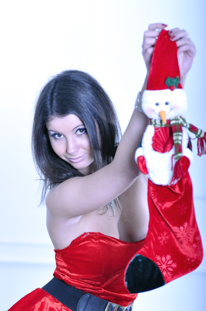 Beautiful young woman in Santa costume holds Christmas Sock photo
