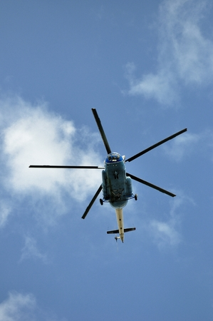 Helicopter flying against the blue sky photo