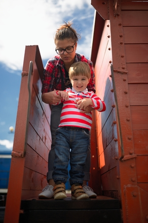 Mother and the son go down from the car of the freight train photo