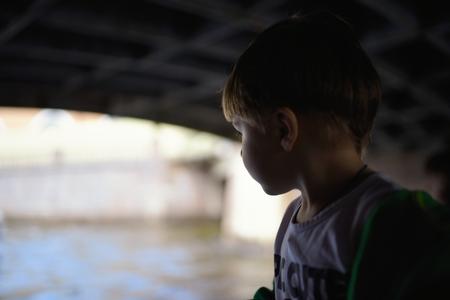 sain: Baby boy on boat looking on water under the bridge in Saint Petersburg Stock Photo