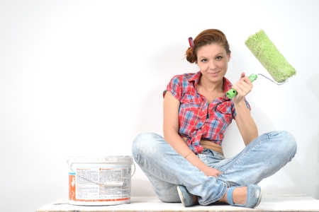 Young beautiful woman sits and thinks of repair Фото со стока