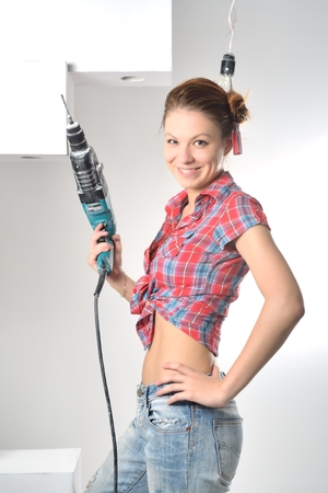 tinkering: Beautiful young woman uses an electric drill Stock Photo