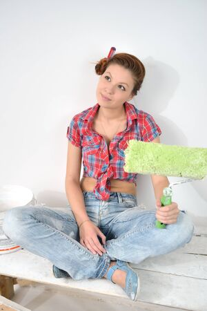 thinks: Beautiful young woman with roller thinks over idea of repair Stock Photo
