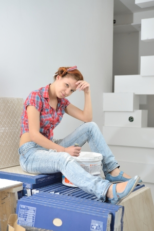 housepainter: Young beautiful woman sits and thinks of repair Stock Photo