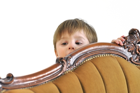 hides: The small child hides behind a sofa and looks out Stock Photo