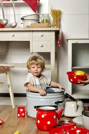 Adorable small child sits in kitchen inside a pan photo