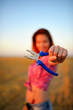 flat nose: Young woman holds flat nose pliers in a hand at field