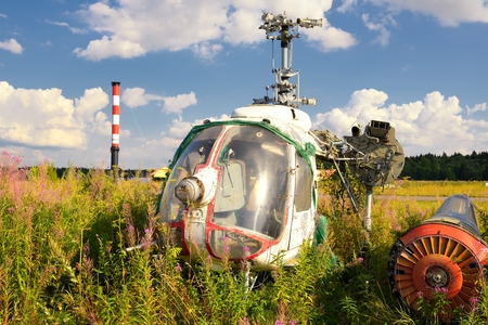 Old airplane fuselage and rusty helicopters on green grass photo