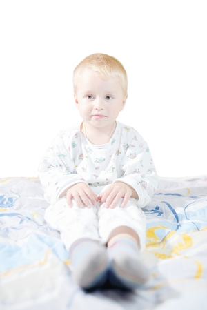 Funny cute little child in pyjamas with blonde hair sits on a bed photo