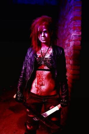 Scary portrait of an angry maniac woman with two machetas in blood in halloween style