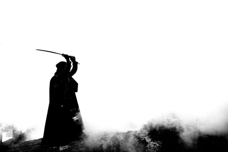 Woman killer holding Japanese sword on a post-apocalyptical landscape