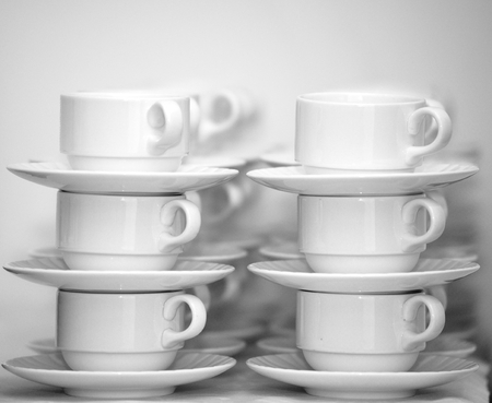 Rows of coffee cups with saucers photo