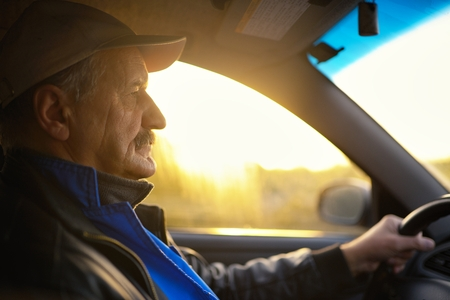 Old man with moustaches driving a car. Sun beams through a glass