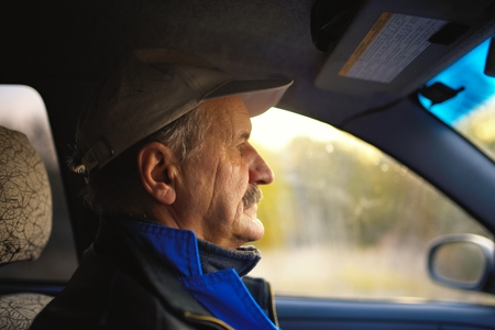 Old man with moustaches driving a car