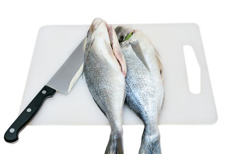 european roach: Two raw fish on a cutting board and knife isolated
