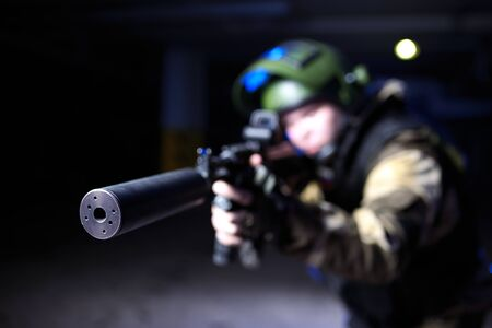 the silencer: Closeup view on silencer on mashine gun in military hands