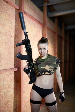 Beautiful sexy brunette woman holding army weapon