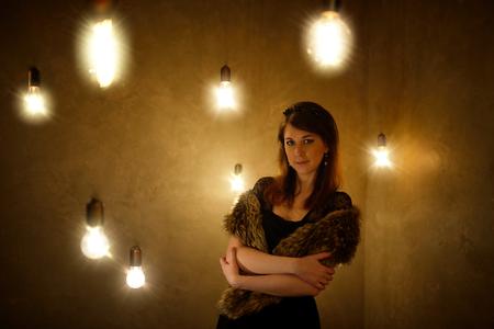 incandescence: Beautiful glamorous woman in fur coat posing at studio with incandescence bulb Stock Photo