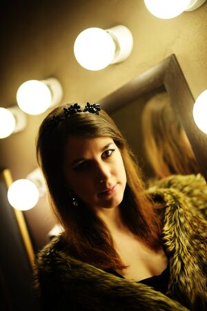 charm temptation: Beautiful glamorous woman in fur coat posing near mirror with bulb Stock Photo