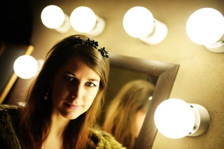 woman in fur coat: Beautiful glamorous woman in fur coat posing near mirror with bulb Stock Photo