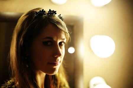 manteau de fourrure: Belle femme glamour en manteau de fourrure posant pr�s du miroir avec ampoule