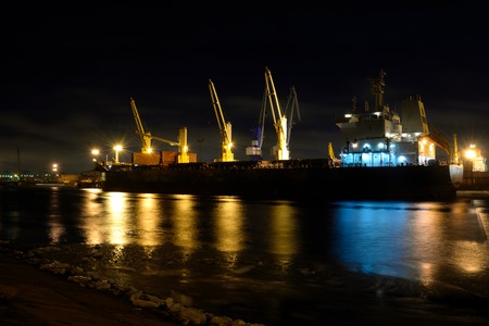 icefield: The loading cargo ship with cranes is moored in port at night Stock Photo