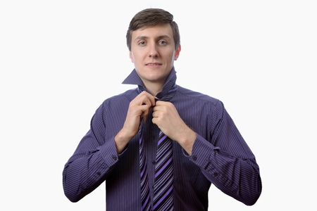Young businessman try to tie one's tie on white background Standard-Bild