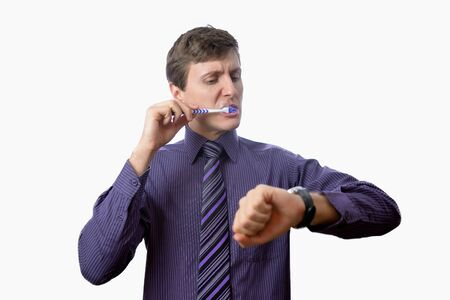 misshapen: Young man brushing his teeth also looks on at watch on white background Stock Photo