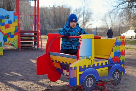 plays: The little boy at a playground plays on the childrens machine