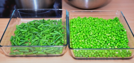 Green peas and bean pods in glasswares Stock Photo