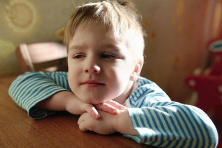 cunning: The amusing child sits at a table and cunning looks Stock Photo