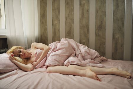 restful: Beautiful young woman sleeps in the bedroom