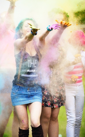 Two girl during Holi festival throw color paints