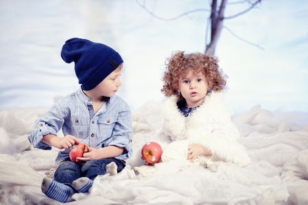 plays: Little boy and girl plays in studio snow forest background