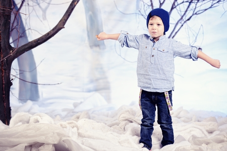 studio happy overall: Little toddler boy in studio with snow and forest background Stock Photo
