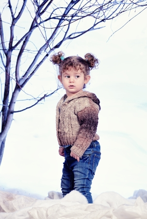 studio happy overall: Little toddler girl in studio with snow and forest background Stock Photo