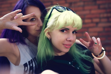 color model: Closeup fashion lifestyle portrait of two young pretty beautiful friends with color hair making selfie