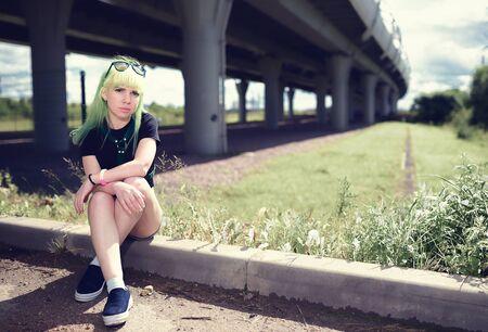 swag: Hermosa mujer bot�n joven con el pelo verde que presenta cerca de camino de la carretera