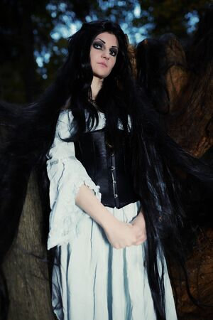 dark elf: Young beautiful witch with long dark hair in root of old tree Stock Photo