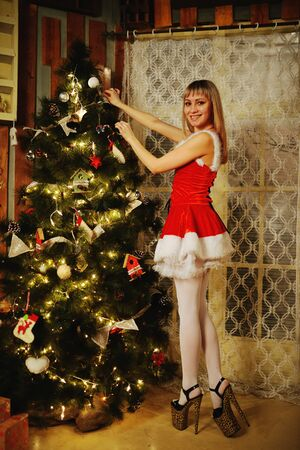 sexy santa claus: Sexy Santa Claus girl putting Christmas ornaments on the tree