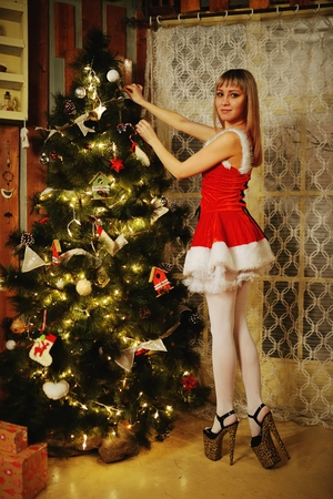 get dressed: Sexy Santa Claus girl putting Christmas ornaments on the tree