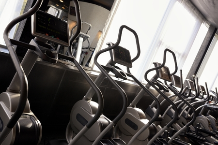 heavy heart: Row of elliptical cross trainer in modern fitnes sport club