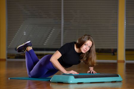 musculine: Sporty girl doing push-ups on platform for an aerobics step Stock Photo