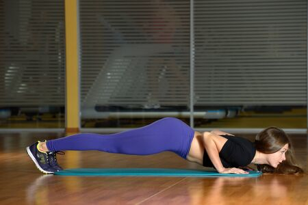 musculine: Sporty girl doing push-ups at gym