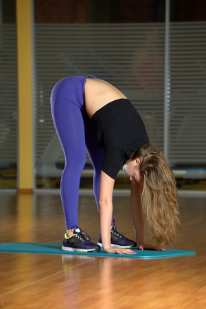 bending down: Sporty girl does an extension bending down