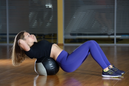 fit ball: Young happy woman doing fitness exercises with fit ball at gym. Swing a press